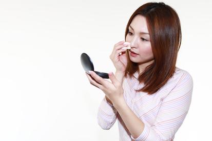 化粧直しをする女性